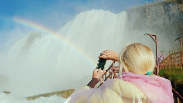 Thumbnail for Tourism in the US - a Woman in a Raincoat Takes Pictures of the Famous Niagara Falls in a Cave of