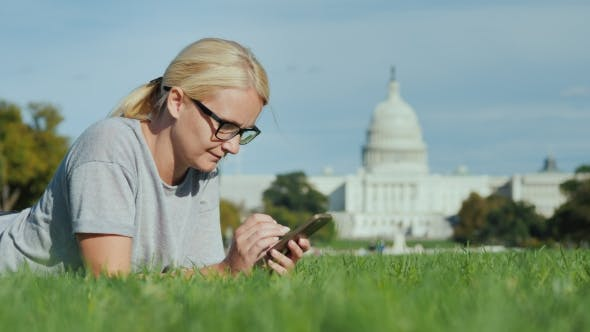Thumbnail for A Woman Lies on a Lawn Against the Background of the Capitol in Washington, DC. Uses a Smartphone