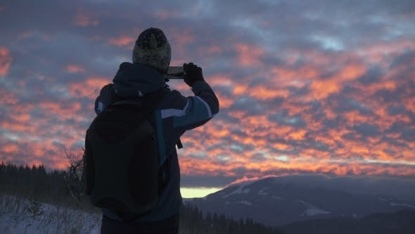 Thumbnail for Tourist Taking Photograph of Sunset in Mountains