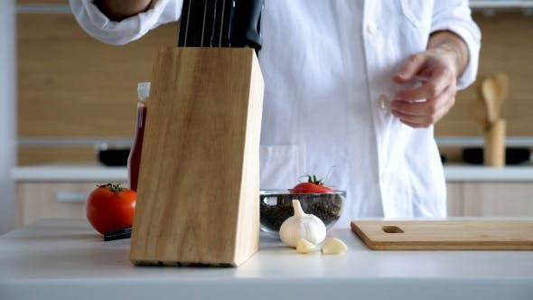 Thumbnail for Chef in Modern Kitchen Sharpens Knife