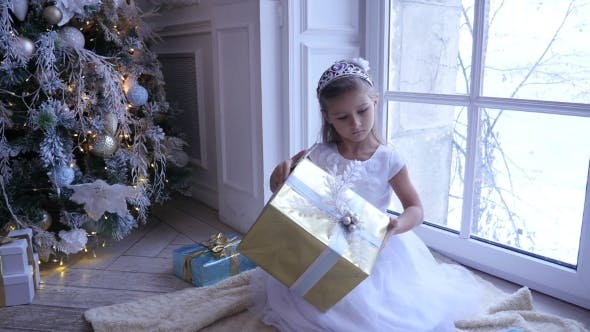 Thumbnail for Little Adorable Girl Sitting Near the Christmas Tree and Looks at Christmas Gift