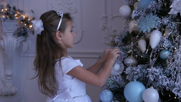 Thumbnail for Child Decorating the Christmas Tree, Little Girl Decorating the Christmas Tree