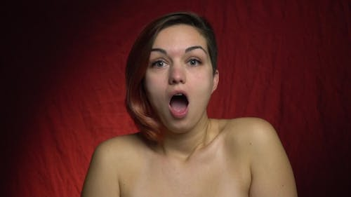 A Woman Stands Topless and Opens Her Mouth in Surprise