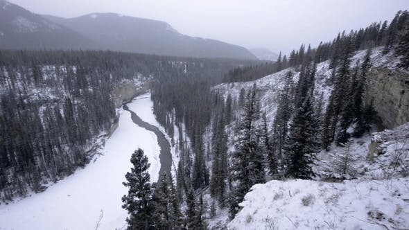 Thumbnail for Icy Winter River Winds Through Canyon Valley in Snowstorm