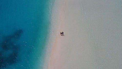 Couple Walking Along Incredible Sandbank in the Maldives