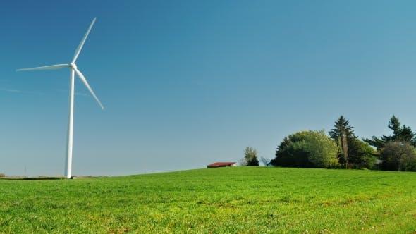 Eine Windturbine steht auf einem Hügel in der Nähe der Farm. Ideales Bild von sauberer Energie