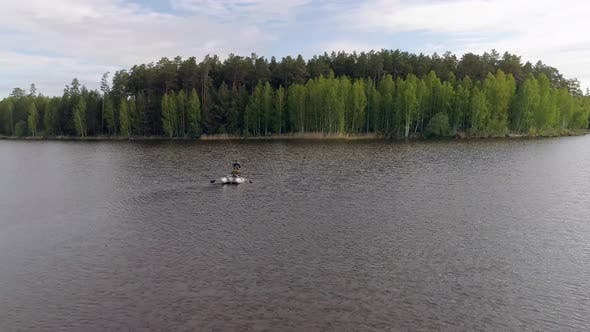 Aerial view of lake surrounded by a forest with two fishermens in a boat fishing