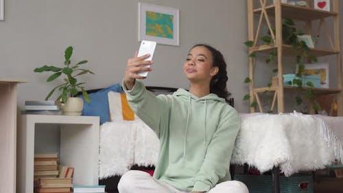 African Teen Girl Using Phone Taking Selfie Posting in Social Media at Home