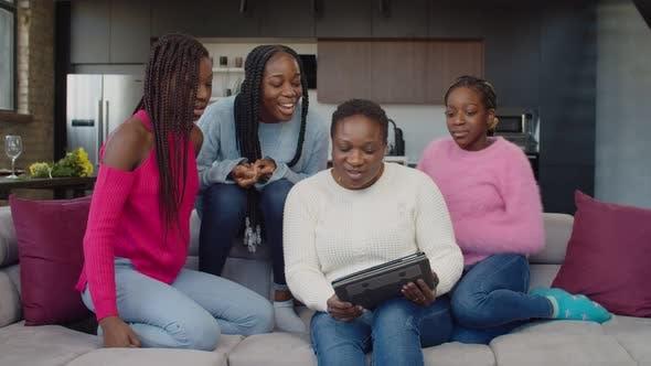 Fröhliche Familie mit drei Teenager-Mädchen, die Videoanrufe mit einem Tablet-PC tätigen