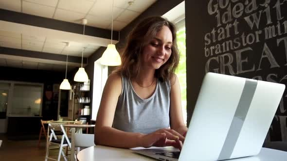 Slow Motion Young Smiling Woman Making Video Call By Laptop at Cafe.