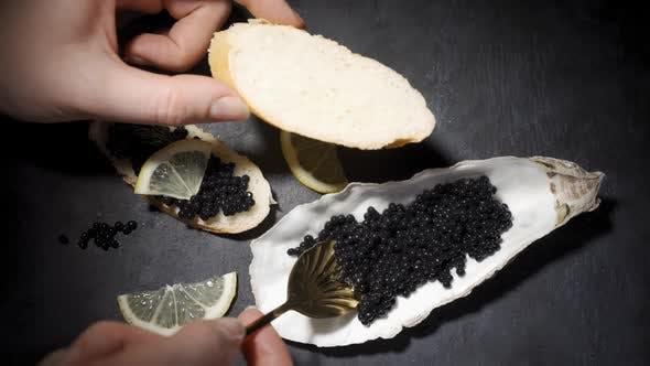 Woman Smears Black Caviar on a Baguette