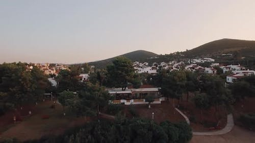 Aerial Panorama of Trikorfo Beach Cottages and Green Hills, Greece