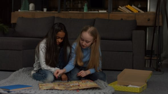 Excited Multiracial Girls Playing Board Game