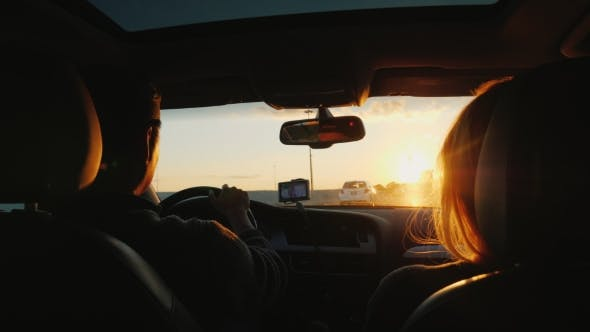 Cover Image for A Young Multi-ethnic Couple Is Driving To the Car in a Sunset. The Light Beautifully Illuminates the