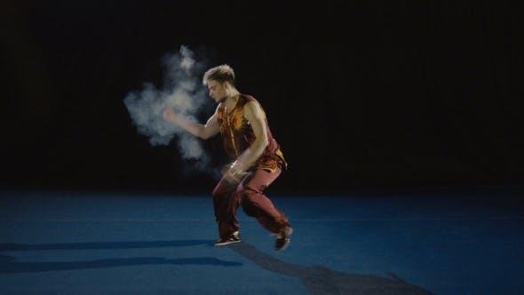 Young Man Training Wushu Against Black Background