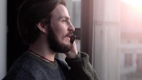 Thumbnail for Man Talks on Phone Near Window