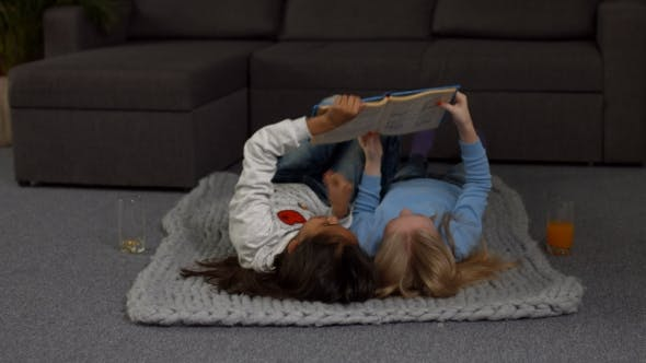 Thumbnail for Playful Children Reading a Book on the Floor