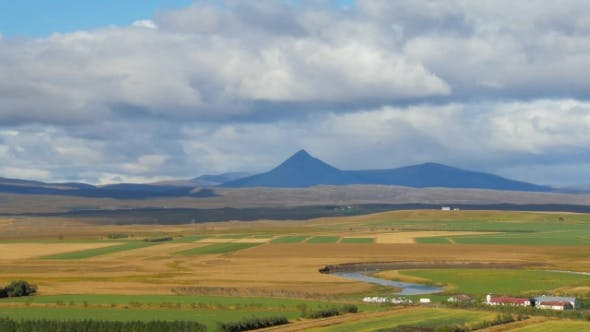 Thumbnail for Agricultural Fields, Meandering River and Dark High Mountain in Icelandic Landscape