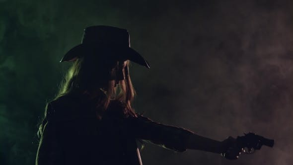 Thumbnail for Cowgirl Holds a Revolver in Her Hands and Aiming at the Villain. Black Smoke Background. . Side View