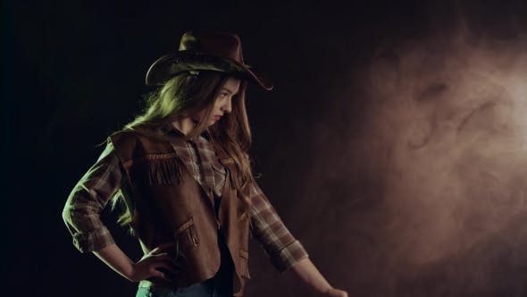 Thumbnail for Cowgirl Takes Out a Revolver and Makes a Shot. Black Smoke Background. . Side View