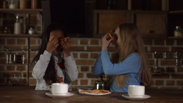 Thumbnail for Funny Girls Covering Eyes with Cookies in Kitchen