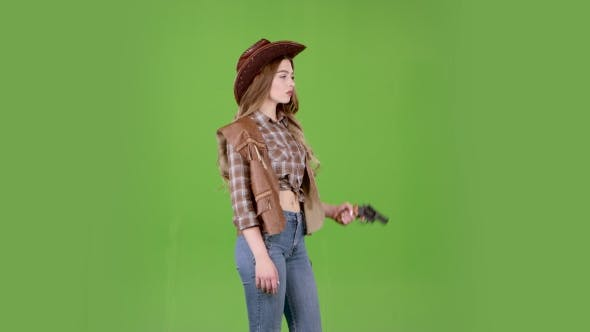 Thumbnail for Girl in a Hat, Cowboy Boots and a Vest Shoots a Revolver. Green Screen