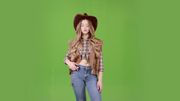 Thumbnail for Girl in the Shape of a Cowboy Is Waiting for Her Friends and Looks at Her Watch. Green Screen