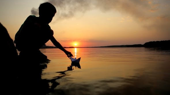 Thumbnail for Boy Playing With Paper Boat