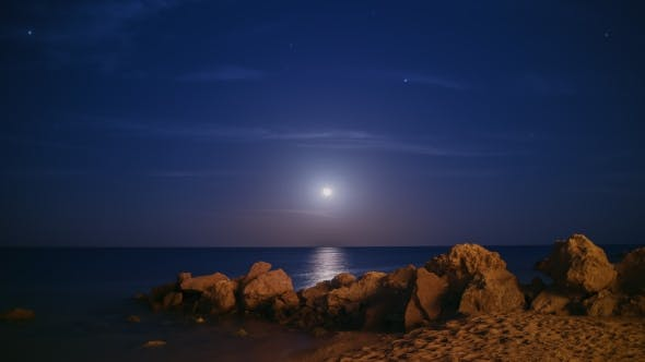 Epic Moon Rising Over the Sea. There Is a Moon Track, Stars and Falling Meteorites