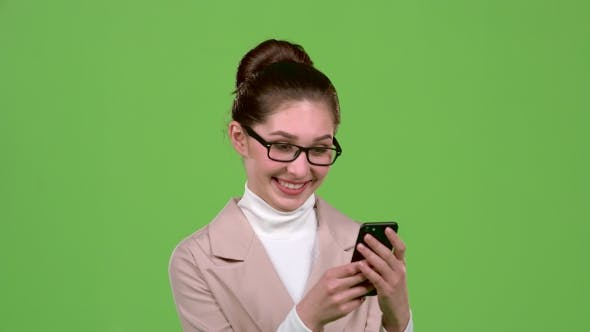 Thumbnail for Business Lady Looks at Photos on Her Smartphone. Green Screen