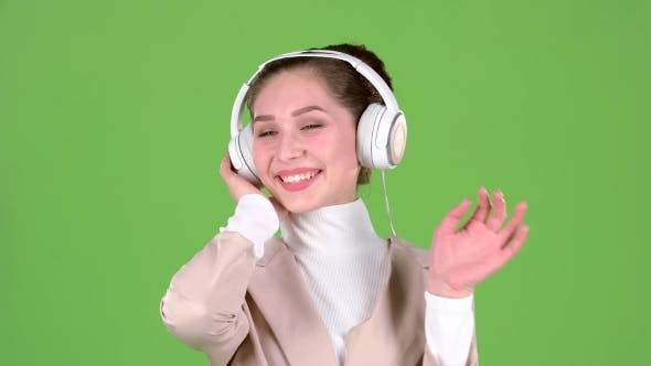 Thumbnail for Woman Listens To Melodious Songs in the Headphones. Green Screen