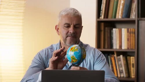 Mature Man Looking at Globe Map of World and Dreaming of Vacation Sitting Near Laptop at Home