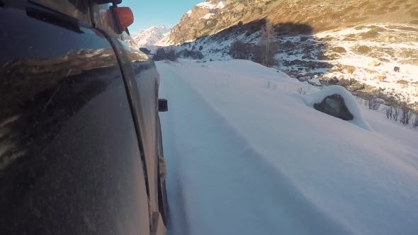 Thumbnail for Wheel of a Car Riding Along a Mountain Road in the Snow