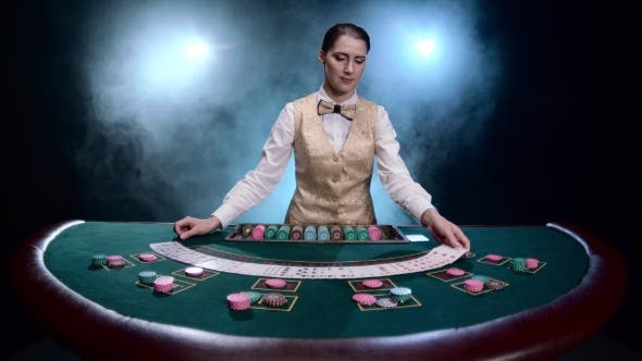 Cover Image for Girl Croupier at a Casino Shuffles Cards on Black Smoky Background with Spotlights.
