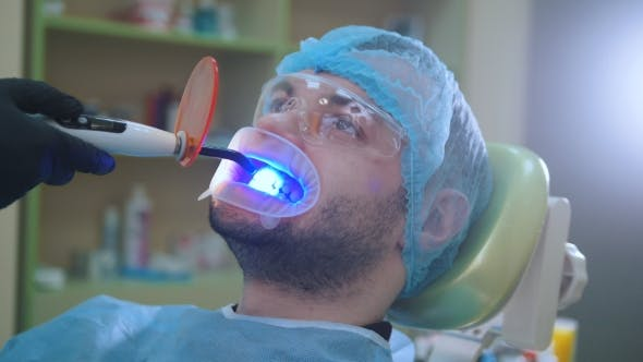 Thumbnail for Doctor and Patient with Retractor in the Dental Office, Cleaning with Ultraviolet Light and Orange