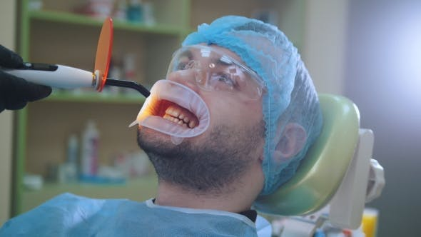 Thumbnail for Doctor and Patient with Retractor in the Dental Office, Ultraviolet and Orange Protective Screen