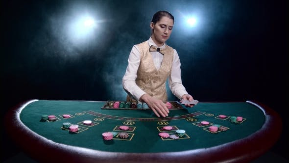 Thumbnail for Girl Croupier at the Chips Table Distributes Cards on Black Smoky Background with Spotlights.