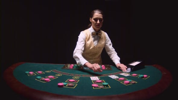 Thumbnail for Casino Dealer Pulls Cards From Card Holder, Lays Chips at a Poker Table. Black Background.