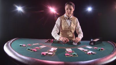 Casino Dealer Handling Playing Cards at a Poker Table. Black Background.