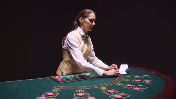 Thumbnail for Poker Game Dealer Hands Out Cards on a Green Table. Black Background.