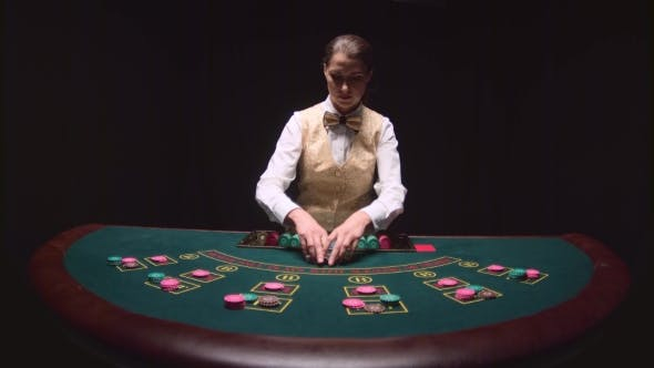 Thumbnail for Casino Female Croupier Distributes for Table Poker Three Cards Are the Flop. Black Background.
