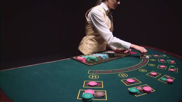 Thumbnail for Casino Croupier Girl Distributes Cards on the Poker Table Top Using Cut Card. Black Background.
