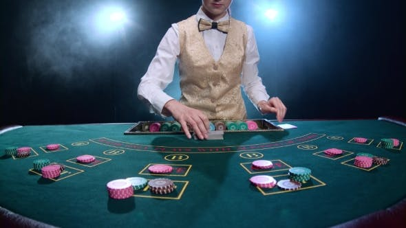 Cover Image for Dealer Handling Playing Cards at a Poker Table. Smoke.