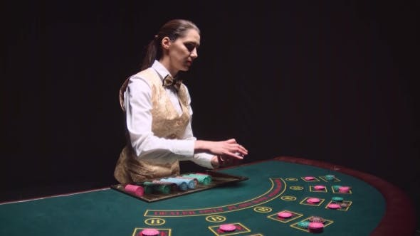Thumbnail for Casino Croupier Girl Distributes Cards on the Poker Table Top. Black Background.