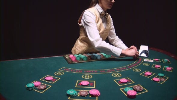 Thumbnail for Casino Female Croupier Takes the Cards From Card Holder at the Game Table. Black Background.