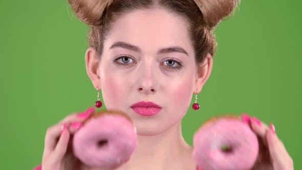Thumbnail for Girl Holds Two Donuts in Her Hands and Closes Her Eyes. Green Screen.