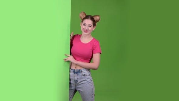 Thumbnail for Mädchen späht aus hinter einem grünen Brett und zeigt ein Ok. Grüner Bildschirm