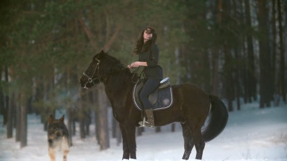 Thumbnail for Professional Beautiful Longhaired Woman Riding a Black Horse Through the Deep Snow in the Forest