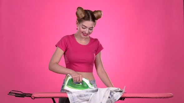 Thumbnail for Girl Ironing Clothes with an Iron on a Pink Board. Pink Background