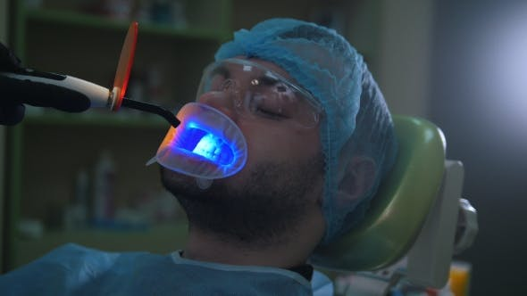 Cover Image for Doctor and Patient with Lip Dilator in the Dental Office, Cleaning and Disinfection with Ultraviolet